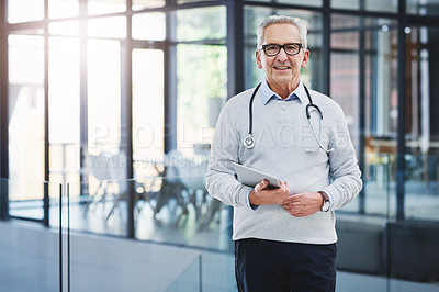Buy stock photo Cropped portrait of a handsome mature male doctor standing with his tablet in the hospital