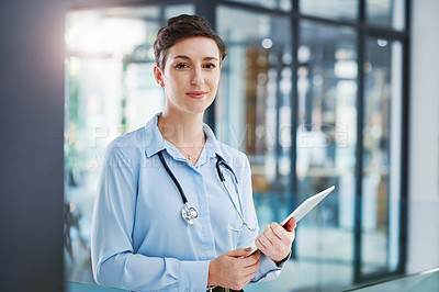 Buy stock photo Cropped portrait of an attractive young female doctor using her tablet while standing in the hospital