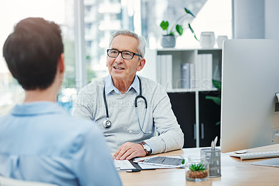 Buy stock photo Cropped shot of a handsome mature male doctor sitting in his office with a female patient