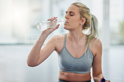 Buy stock photo Shot of a sporty young woman drinking water while exercising in a studio