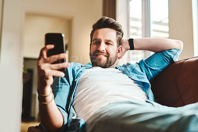 Buy stock photo Cropped shot of a handsome young man using a cellphone while chilling on the sofa at home