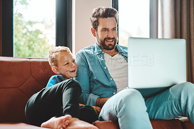 Buy stock photo Cropped shot of a father and son sitting on the sofa using a laptop at home