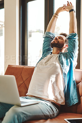 Buy stock photo Cropped shot of a handsome young man stretching while using a laptop on the sofa at home