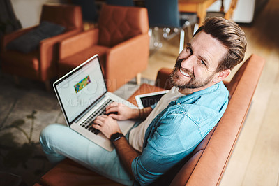 Buy stock photo High angle shot of a handsome young man using a laptop while chilling on the sofa at home
