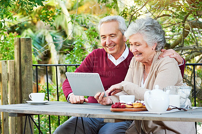 Buy stock photo Cropped shot of a senior couple using their tablet while having breakfast together outside