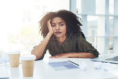 Buy stock photo Portrait of a young businesswoman sitting at her office desk looking tired and stressed out