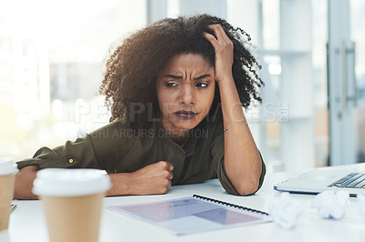 Buy stock photo Shot of an attractive young woman sitting in an office environment looking confused and a bit stressed out