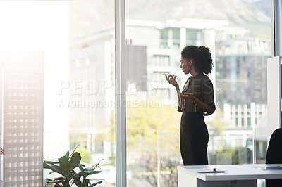 Buy stock photo Shot of a young businesswoman standing in a office and busy talking on her smartphone