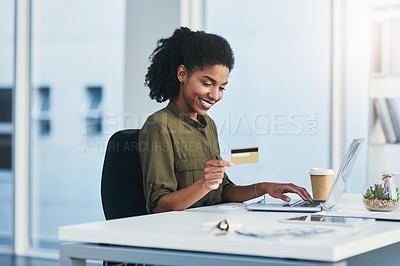 Buy stock photo Shot of a young businesswoman using her laptop and credit card in a modern office