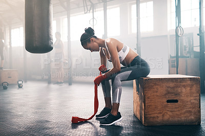 Buy stock photo Full length shot of an attractive and athletic young woman strapping her wrists while sitting in the gym