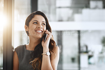 Buy stock photo Cropped shot of an attractive young businesswoman looking thoughtful while making a phonecall in her office