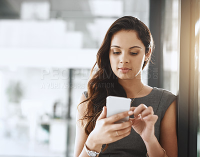 Buy stock photo Cropped shot of an attractive young businesswoman sending a text message while working in her office
