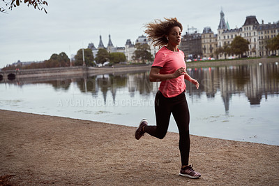 Buy stock photo Full length shot of an attractive young woman jogging alongside a lake outdoors