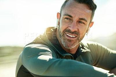 Buy stock photo Shot of a mature man using wireless earphones while out for his workout