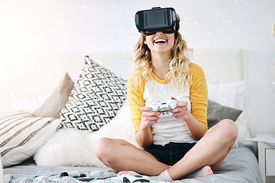 Buy stock photo Full length shot of an attractive young woman gaming using a vr headset while sitting on her bed at home