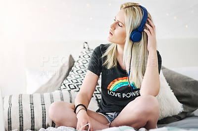 Buy stock photo Full length shot of an attractive young woman listening to music while relaxing on her bed at home