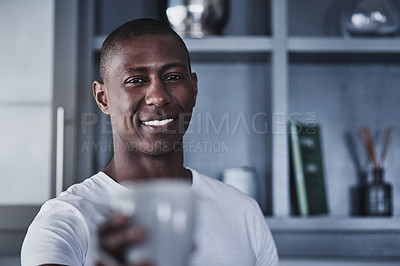 Buy stock photo Portrait of a young man having coffee during a relaxing morning at home