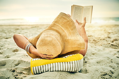 Buy stock photo Full length shot of an unrecognizable young woman reading a book while lying on the beach