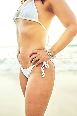 Buy stock photo Cropped shot of an unrecognizable young woman standing with her hands on the hips on the beach