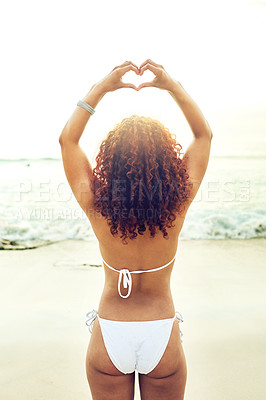 Buy stock photo Rearview shot of an unrecognizable young woman making a heart shape with her hands while standing on the beach