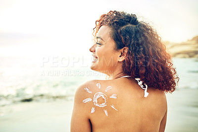 Buy stock photo Rearview shot of an attractive young woman posing with sunscreen on her back at the beach