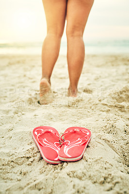 Buy stock photo Shot of sandals on the beach with an unrecognizable young woman standing in the background
