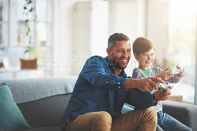 Buy stock photo Shot of a cheerful little boy and his father playing video games together on the television while being seated on the sofa at home during the day