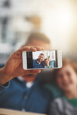 Buy stock photo Closeup of a cheerful little boy and his father taking a self portrait together while being seated on the sofa together