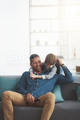 Buy stock photo Shot of a cheerful little boy and his father playing around together while being seated on a sofa together at home