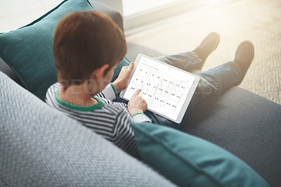 Buy stock photo Shot of a focused little boy browsing on a digital tablet while being seated on a sofa at home during the day