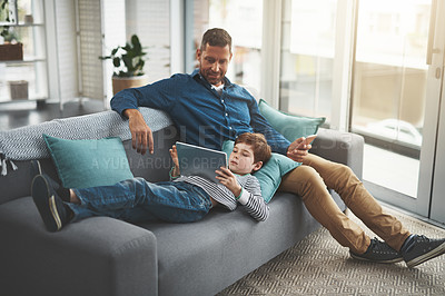 Buy stock photo Shot of a cheerful little boy browsing on a digital tablet while lying on his father's lap at home during the day