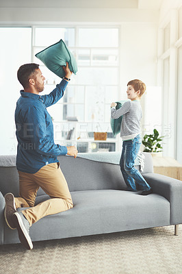 Buy stock photo Shot of a cheerful little boy and his father having a pillow fight together in the living room at home during the day
