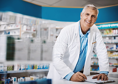 Buy stock photo Shot of a male pharmacist writing on a clipboard in a drugstore