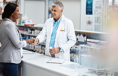 Buy stock photo Shot of a male pharmacist assisting a customer in a chemist