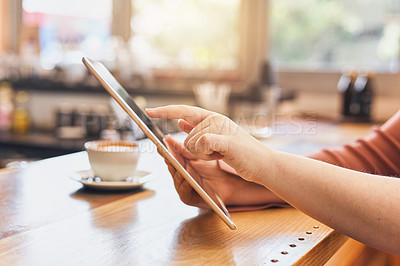Buy stock photo Shot of an unrecognizable young woman blogging while sitting in a coffee shop