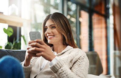 Buy stock photo Shot of an attractive young woman sending text messages while relaxing on her sofa at home