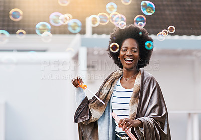 Buy stock photo Shot of a carefree young woman blowing bubbles in the backyard