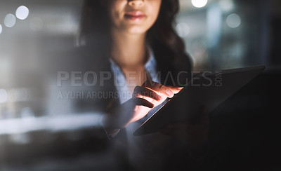 Buy stock photo Cropped shot of an unrecognizable young businesswoman using her tablet while working late in the office