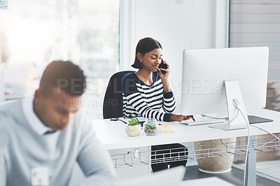 Buy stock photo Shot of a young businesswoman taking a phone call at her office desk with a colleague working in the foreground
