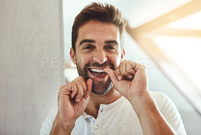 Buy stock photo Cropped portrait of a handsome young man flossing his teeth while looking at his reflection in the mirror at home