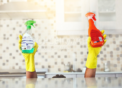 Buy stock photo Cropped shot of an unrecognizable young man holding up bottles of detergent while cleaning his home