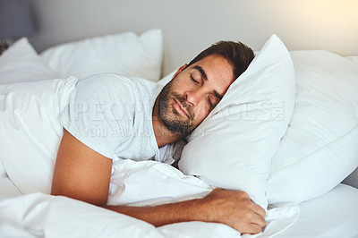 Buy stock photo Cropped shot of a handsome young man sleeping comfortably in his bed at home