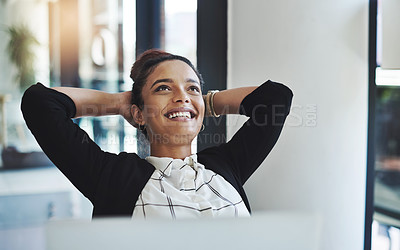 Buy stock photo Shot of a young businesswoman relaxing at her desk in a modern office