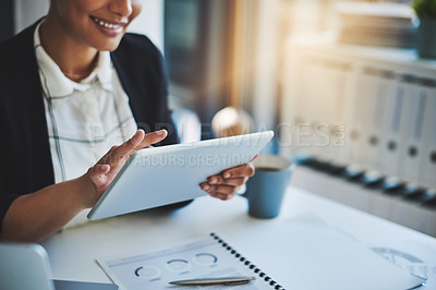Buy stock photo Cropped shot of a young businesswoman using a digital tablet in a modern office