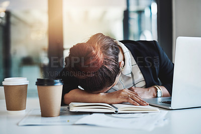 Buy stock photo Shot of a young businesswoman sleeping at her desk in a modern office