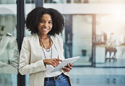 Buy stock photo Portrait of a young businesswoman smiling and holding a digital tablet in her office