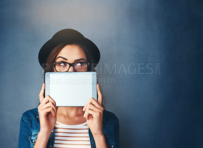 Buy stock photo Shot of an attractive young woman holding tablet in front of her face in studio