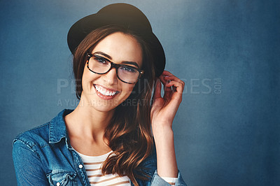 Buy stock photo Studio portrait of an attractive young woman smiling against a blue background