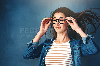 Buy stock photo Studio shot of a young woman with air being blown in her face against a blue background