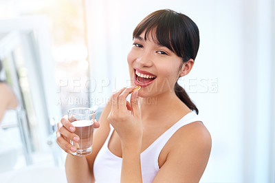 Buy stock photo Portrait of a cheerful attractive young woman taking medication at home during the day